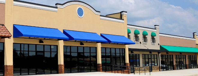 blue awnings covering entrance and windows on new retail building