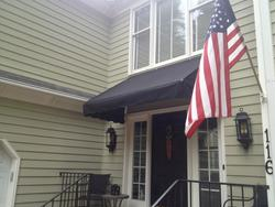 black door awning with American flag next to it on the house